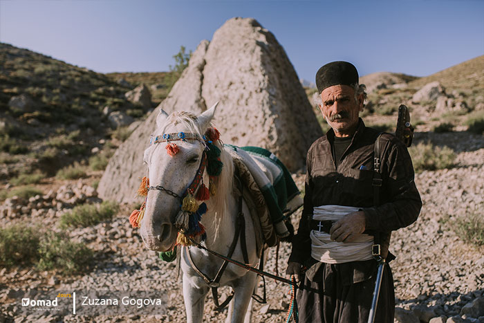 old nomadic man wearing traditional dresses near her horse