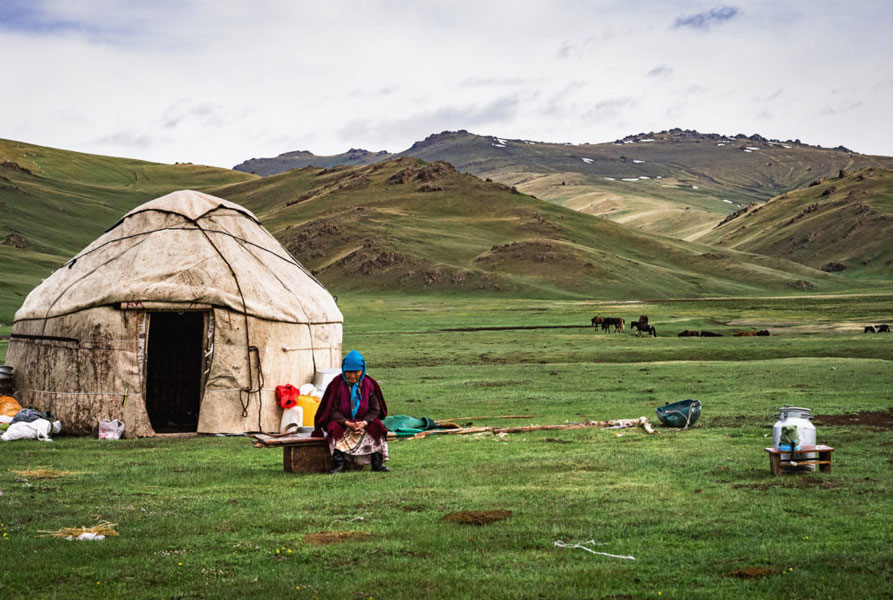 A large green pasture with a yurt camp and a nomad in the middle