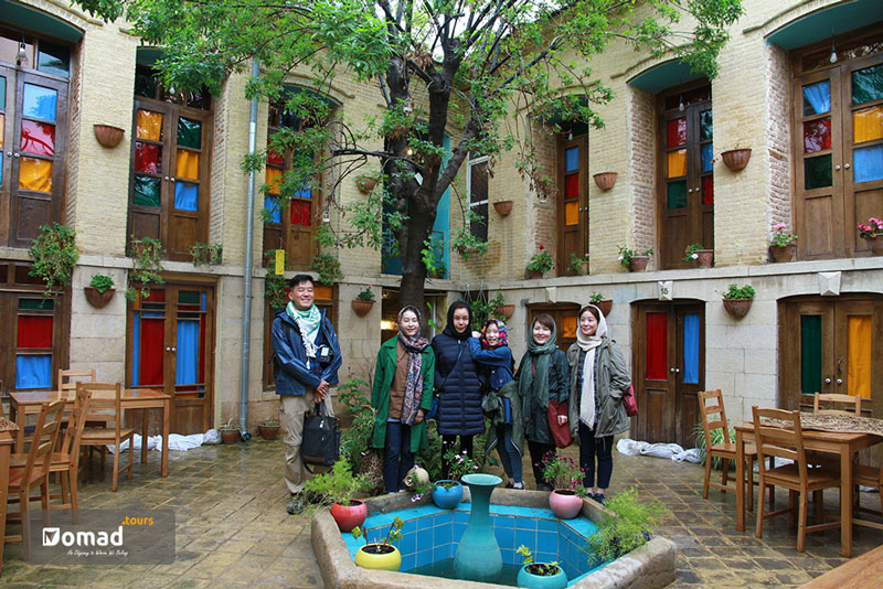 a group of smiling tourists gathered in the yard of a traditional eco lodge with colorful windows in Shiraz, Iran.
