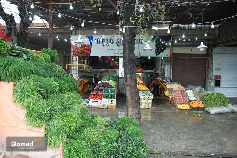 A traditional grocery shop displays heaps of fresh green herbs and boxes of colorful locally-picked fruits.