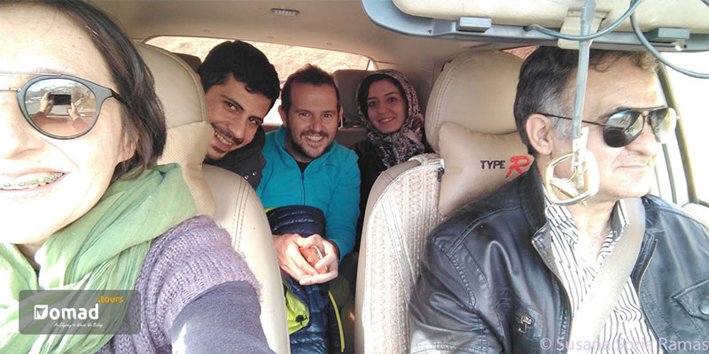 a group of tourists smile in the car and try to fit in the photo while driving to their destination
