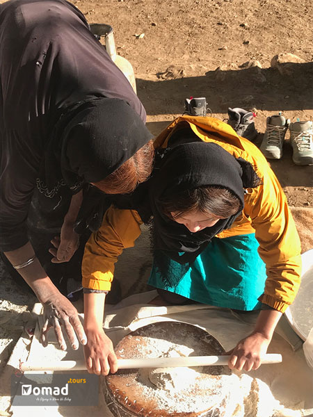 A nomadic woman dressed in black is showing a tourist how to knead the dough to make traditional flatbread