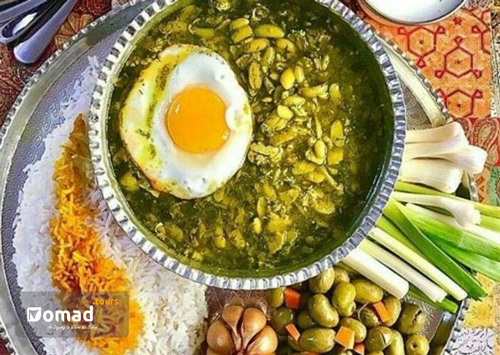 A vegetarian Persian dish with egg & beans surrounded by rice, garlic, onion & olive, served in copper dishes