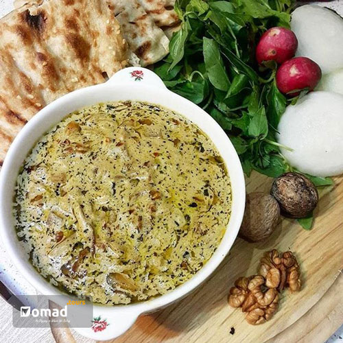 A nutritious vegetarian Persian dish made of walnuts, mint and kashk which is served in a white Persian dish and there are Sangak bread & vegetable beside it