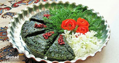 A Vegetarian Persian dish made of vegetable, egg and walnut. It is served in a copper dish and decorated with tomatoes and vegetables