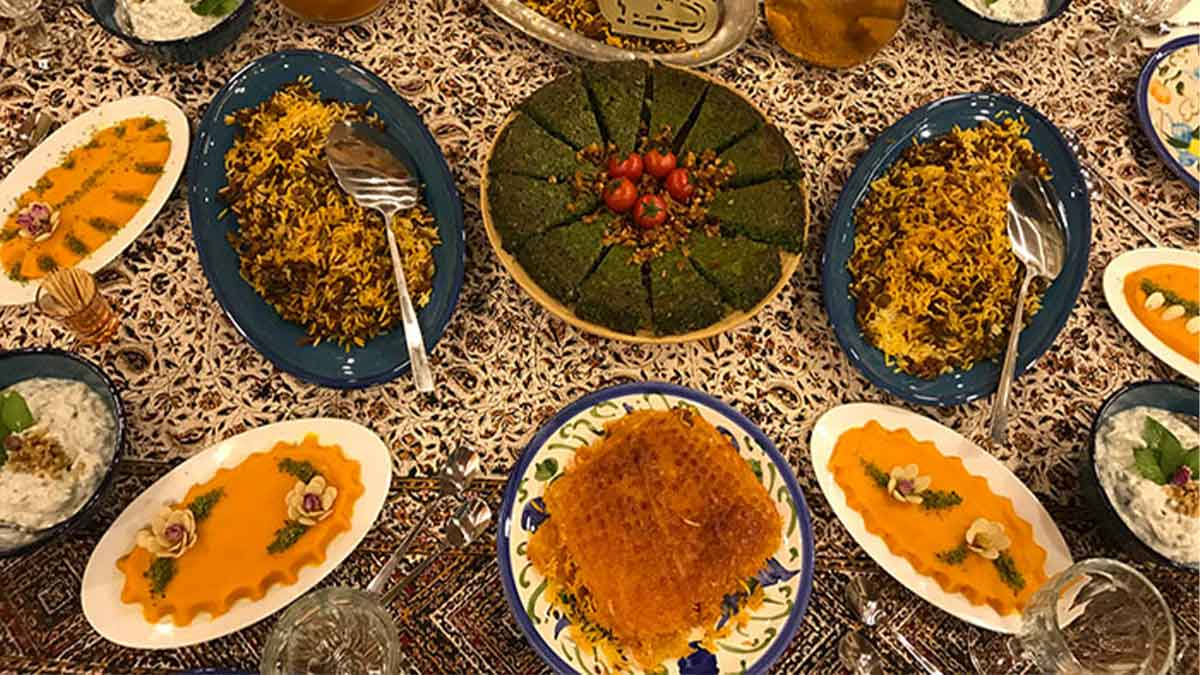 A table of different Persian dishes; two dishes of rice served on blue dishes, Tahdig, Koko Sabzi and Saffron rice pudding