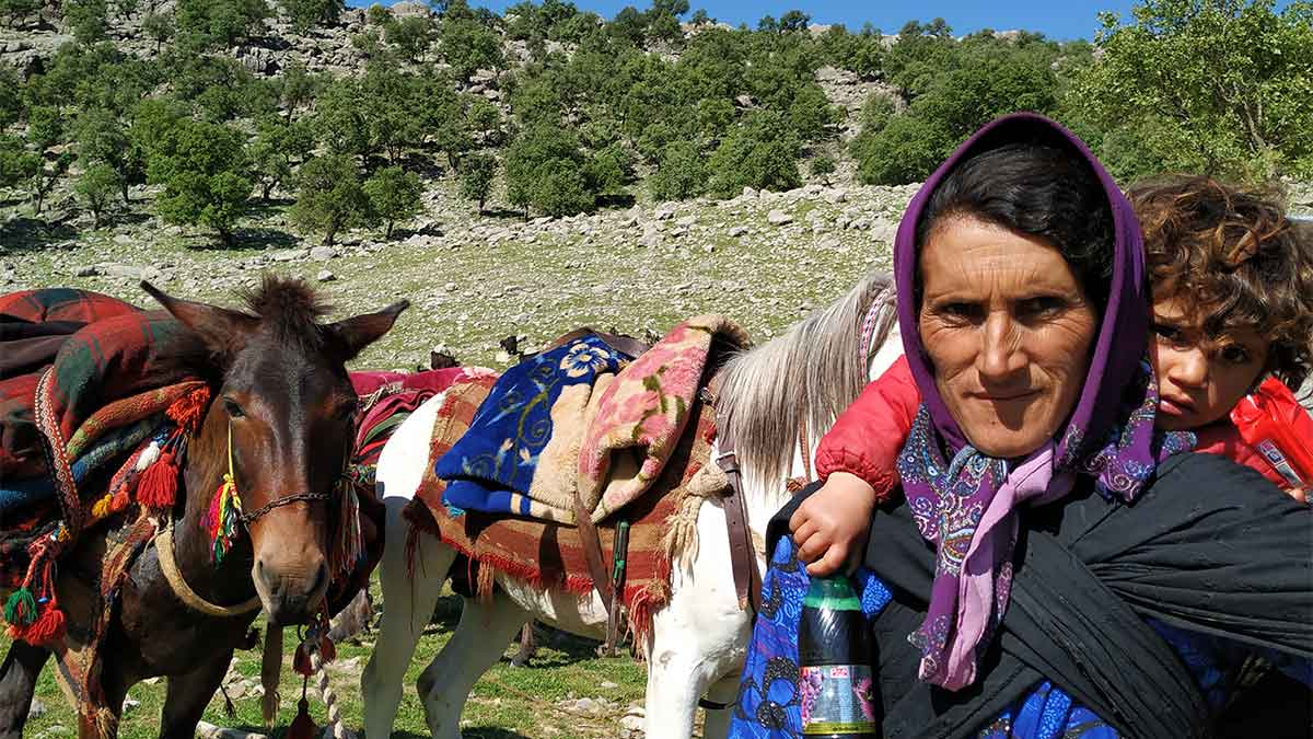 a Bakhtiari nomad woman with a child on her back, and a brown Persian horse beside her