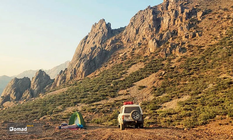Mighty Zagros mountains and a green camp of travelers who have spent the night sleeping in nature