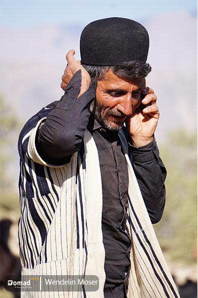 A Bakhtiari nomad man wearing Choogha and talking on his phone