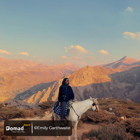 Emily Garthwaite on a white Persian horse among Mt. Zagros ranges