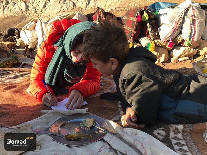 Emily Garthwaite is writing her notes and Kianoush, the nomad boy, is looking carefully at her notes. Their breakfast, honey & ghee, is on a plate in front of them