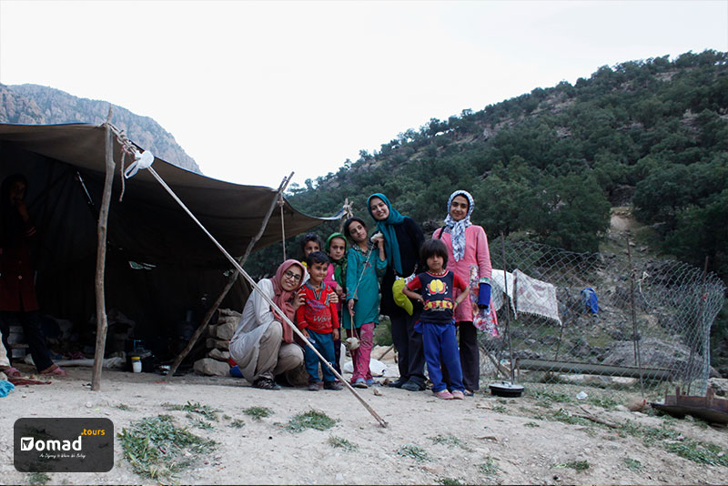 A black nomadic tent in Mt. Zagros with a group of nomad children and some members of IRANomad's team