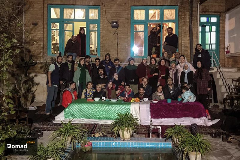 An old Iranian house with a blue torquiest-tiled pool and blue windows. A lot of people are standing around two korsis in Yalda night