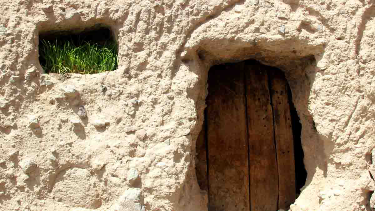 A wooden door in man-made caves in Maymand village